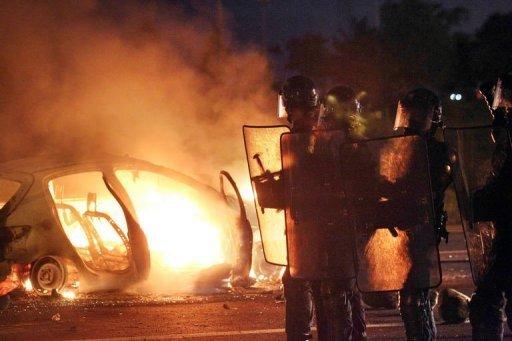 Une voiture brûle devant les forces anti-émeutes au Port, sur l'île de La réunion, le 19 février 2013 (AFP, Richard Bouhet)